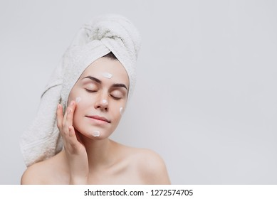 Skin care. A cute young  girl with a towel on her head puts a nourishing cream on her face. Causing moisturizer cream onto her face . Place for text