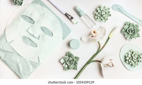 Skin care flat lay with facial sheet mask, mist spray bottle , succulents and orchid flowers on white desktop background, top view. Beauty spa and wellness concept