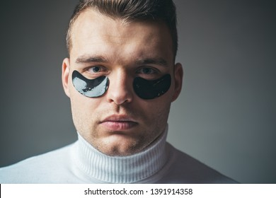 Skin care. Focused treatments for under eye area. Minimizes puffiness and reduce dark circles. Eye patches for men. Man with black eye patches close up face. Beauty treatment. Metrosexual concept.