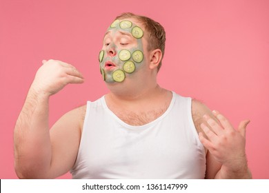 Skin care and grooming, self-care concept. Comic positive man with cucumber and clay mask blows on his nails as if drying nail polish