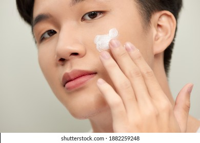 Skin care. Handsome young man applying cream at his face and looking at himself with smile while standing over white background