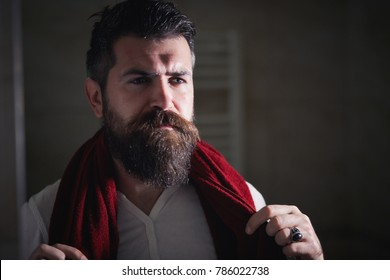 Skin care. Handsome young man in a white T-shirt, looking at himself with a serious face, standing in front of the mirror. Portrait of a bearded man looking in the mirror in his bathroom. morning
