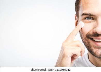 Skin care. Handsome young shirtless man applying cream at his face and looking at himself with smile while standing over gray background and looking at camera. Close-Up. Space for text.