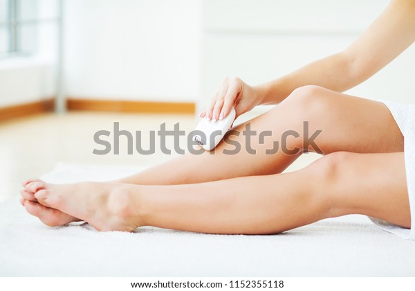 Skin Care and Health. Hair Removal. Woman Epilating Leg, White Electric Epilator.