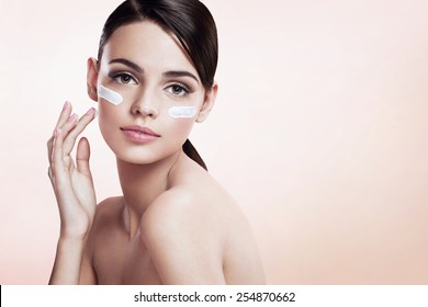 Skin care lady putting face cream / photoset of attractive brunette girl on beige background. Copy space