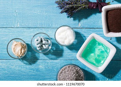 skin care and makeup product samples on blue wooden table background