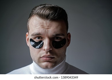 Skin care. Minimizes puffiness and reduce dark circles. Eye patches for men. Man with black eye patches close up face. Beauty treatment. Metrosexual concept. Focused treatments for under eye area.