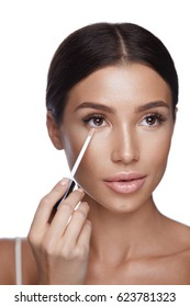 Skin Care. Portrait Of Beautiful Sexy Female With Natural Makeup Applying Corrector On Perfect Fresh Skin. Closeup Of Attractive Woman Applying Concealer With Brush. Beauty Face. High Resolution