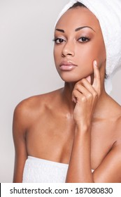 Skin care. Portrait of beautiful young Afro-American shirtless woman holding finger on cheek and looking at camera while isolated on gray background