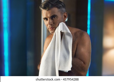 Skin Care. Portrait Of Handsome Man Touching His Face, Wiping His Smooth Skin With Towel While Standing With Naked Upper Body In Bathroom. Hygiene Concept