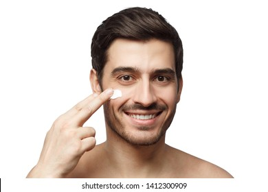 Skin care. Portrait of handsome young man applying cream to his face, isolated on white background