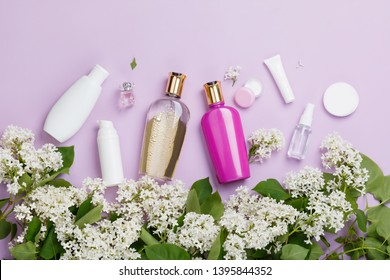 Skin care products (tonic or lotion, serum, cream, micellar water, sea salt, cotton pads) on purple background with spring white lilac blossom. Freshness natural hair care. Shampoo and conditioner