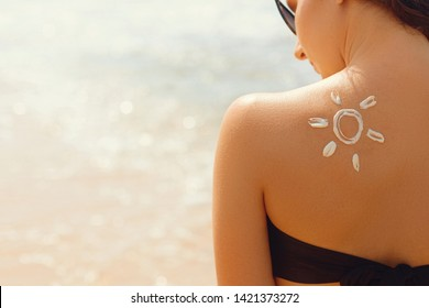 Skin care.Sun protection. Beautiful woman in bikini apply sun cream on Face. Woman with Suntan lotion on beach. Portrait of female holding moisturizing sunblock. The girl uses sunscreen for her skin