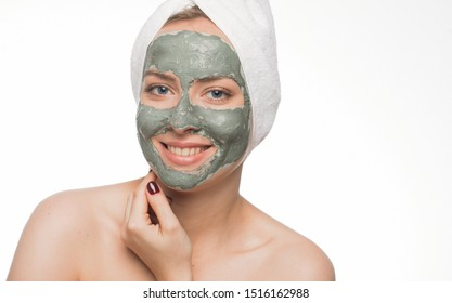 Skin care and spa treatments.Emotional portrait of a happy and satisfied beautiful nude woman with a blue clay cosmetic mask on her face looking with a smile in the mirror isolated on white background