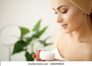 Skin care. Studio shot of beautiful young woman applying moisturizer cream onto her face