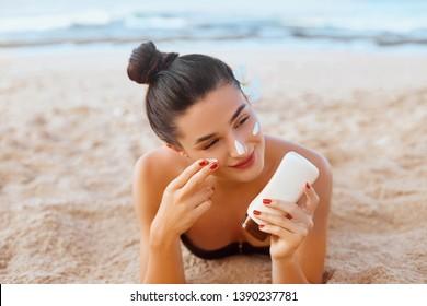 Skin care. Sun protection. Beautiful Woman In Bikini apply sun cream on Face. Woman With Suntan Lotion On Beach. Portrait Of Female Holding Moisturizing Sunblock.The Girl Uses Sunscreen for Her Skin.