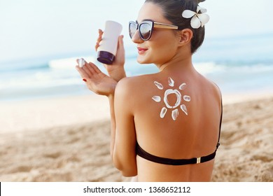 Skin care. Sun protection. Woman apply sun cream. Girl Holding Moisturizing Sunblock. Woman With Suntan Lotion On Beach In Form Of The Sun. Portrait Of Female With  Drawn Sun On A Shoulder. Suncream.