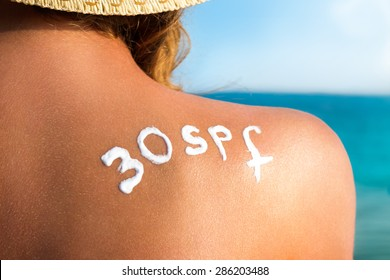 skin care and sun protection, woman with sunscreen lotion on back at the sea shore