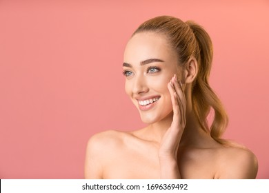 Skin Care Treatment. Cheerful Girl Touching Face Applying Cream Looking Aside Posing Over Pink Background. Free Space, Studio Shot