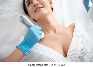 Skin care and treatment. Close up top angle portrait of young pretty brunette lady enjoying of rejuvenation massage of decollete zone in spa center by therapist