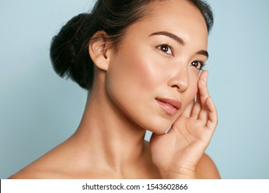 Skin care. Woman with beauty face and healthy facial skin portrait. Beautiful asian girl model with natural makeup touching glowing hydrated skin on blue background closeup. High quality image - Shutterstock ID 1543602866