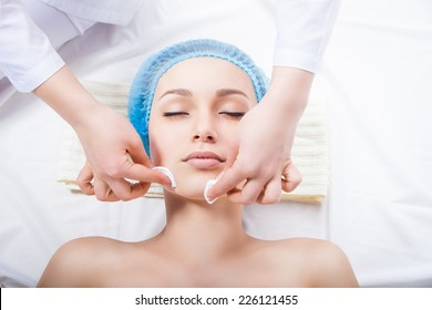 Skin care - woman cleaning face by beautician over white background