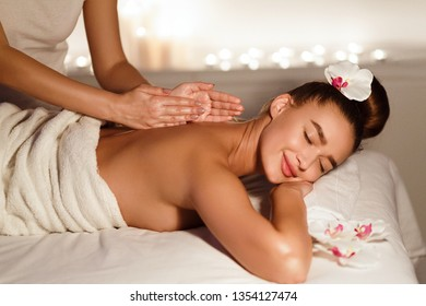 Skin care. Woman enjoying relaxing back massage in cosmetology spa centre