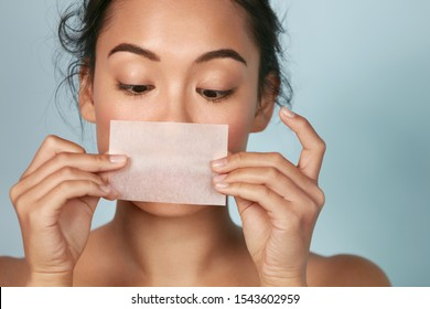 Skin care. Woman holding facial oil blotting paper portrait. Closeup of beautiful asian girl model with natural face makeup looking at oil absorbing tissue, beauty product.
