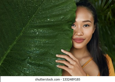 Skin care. Woman model with beauty face and natural green leaf plant. Portrait of beautiful asian girl with nude nails and sexy smile in tropical nature