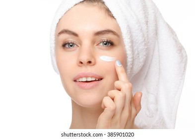 Skin care woman putting face cream touching under eyes. Facial beauty closeup of beautiful female model on white background.