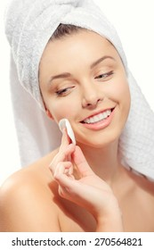 skin care woman removing face makeup with cotton swab pad - skin care concept. Facial closeup of beautiful Caucasian model with perfect skin. Girl isolated on white background