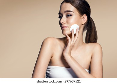Skin care woman removing face makeup - skin care concept / photos of appealing brunette girl on beige background