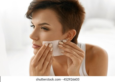 Skin Care. Woman Removing Oil From Face Using Blotting Papers. Closeup Portrait Of Beautiful Healthy Girl With Nude Makeup Cleaning Perfect Soft Skin With Oil Absorbing Tissue Sheets. Beauty Concept