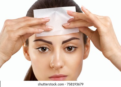 Skin Care. Woman removing oil from face using blotting papers. Closeup Portrait Of Beautiful Healthy Girl With Nude Makeup. Perfect Soft Skin With Oil Absorbing Tissue Sheets. Beauty Concept