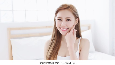 skin care woman touch face on the bed at home