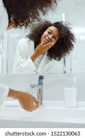Skin care. Woman washing face with clean water in sink looking in mirror at bathroom. Portrait of beautiful smiling african girl with afro hair in white bath robe cleaning facial skin closeup