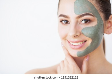 Skin Care. Young Woman With Cosmetic Clay Mask Holding Cucumber At Her Bathroom.