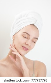 Skin care. Young woman on white background with towel on head touching her clean skin on the face