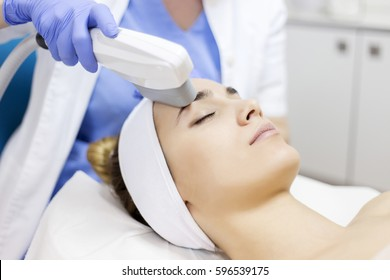 Skin care. Young woman receiving facial beauty treatment, Intense pulsed light therapy. Photo facial therapy. Anti-aging procedures.