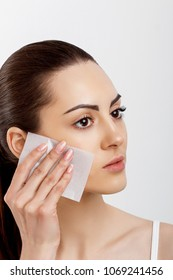 Skin care. Young woman removing oil from face using blotting papers. Photo of beautiful woman with smooth and healthy skin. Beauty concept