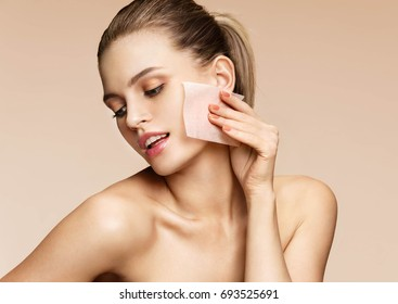 Skin care. Young woman removing oil from face using blotting papers. Photo of beautiful woman with smooth and healthy skin on beige background. Beauty concept