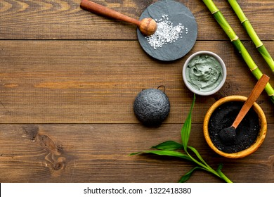 Skin cleansing and detox. Bamboo charcoal powder cosmetics on dark wooden background top view space for text