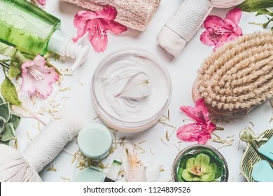 Skin cream with flowers petals and others body care cosmetic products and accessories on white background, top view
