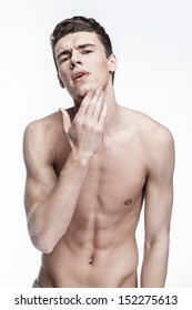 Skin problems - shirtless young man on light background looking at his face