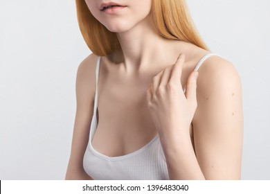 Skin protection Cropped image Young blonde woman's hand is touching her smooth skin on the shoulder Close-up photo