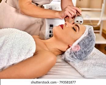 Skin resurfacing procedure facial procedure on ultrasound face machine. Female acne treatment. Test new medical equipment. Woman receiving electric lift massage at spa salon.