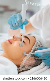 Skin treatment. Nice young woman closing her eyes while having a microcurrent therapy session