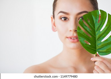 Skincare. Beautiful Woman Portrait on White Background With Clean Skin and Green Leaf in Hand.
