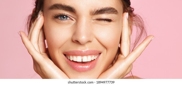 Skincare and beauty. Close up of smiling young woman winking at camera, touching shiny healthy skin, nourished face after tea tree and lemon facial serum and moisturizer, pink background.