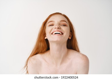 Skincare and beauty. Close-up of beautiful pale redhead female posing naked on white background, smiling happy and laughing, standing naked on studio background.